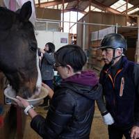 馬術の練習を終えて愛馬のオロバスに「ありがとうな」と声をかける宮路満英さん。左は妻の裕美子さん=山梨県北杜市で2020年2月28日、宮間俊樹撮影