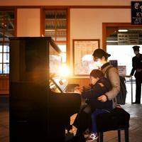 待合室に置かれたピアノを弾く親子=奈良市で2020年2月27日、山田尚弘撮影