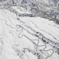 雪山にシュプールを描くように除雪作業が進んでいる立山黒部アルペンルート=富山県立山町で2020年3月19日午後、本社ヘリから