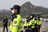 South Korean police officers wearing face masks stand guard near the U.S. embassy in Seoul, South Korea, on March 20, 2020. (AP Photo/Ahn Young-joon)