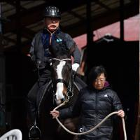 馬術の練習に向かう宮路満英さん。右下は妻の裕美子さん=山梨県北杜市で2020年2月28日、宮間俊樹撮影