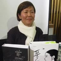 日本語版(左)と原書を手にする筆者のキムさん=東京都新宿区で