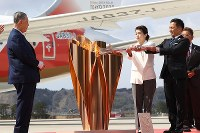 The flame of the 2020 Tokyo Olympics is moved to the larger version of the torch by Olympic gold medalists Saori Yoshida, center, and judoka Tadahiro Nomura, right, at the Japan Air Self-Defense Force's Matsushima Base in the city of Higashimatsushima, Miyagi Prefecture, on March 20, 2020. (Mainichi/Yuki Miyatake)