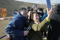 A family takes a selfie with the Olympic flame on the same day it arrived in Japan from Greece, at a park in Ishinomaki, Miyagi Prefecture, on March 20, 2020. (Mainichi/Daisuke Wada)