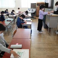 席の間隔が空いた教室で通知表を受け取る児童たち=大阪市天王寺区で2020年3月24日午前9時42分、小出洋平撮影