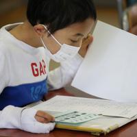 マスク姿で通知表を見る児童=大阪市天王寺区で2020年3月24日午前9時46分、小出洋平撮影