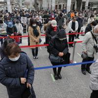 福島駅前で「復興の火」として展示される東京オリンピックの聖火を見るため並び、東日本大震災の犠牲者を悼み黙とうする人たち。新型コロナウイルスの世界的流行をうけ、間隔をあけて並ぶよう促され、入り口で消毒とマスク着用が呼びかけられた=福島市で2020年3月24日午後2時33分、和田大典撮影