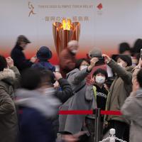 福島駅前で「復興の火」として展示される東京オリンピックの聖火を背に記念撮影する家族連れ。新型コロナウイルスの世界的流行をうけて、マスクの着用や入り口での消毒が呼びかけられた。聖火の前での時間は15秒に限られ、間隔をあけて列をなす人たちが次々に写真を撮っていった=福島市で2020年3月24日午後3時40分、和田大典撮影