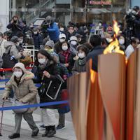 福島駅前で「復興の火」として展示される東京オリンピックの聖火を見物する人たち=福島市で2020年3月24日午後3時2分、和田大典撮影