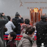 雪が舞う中、福島駅前で「復興の火」として展示される東京オリンピックの聖火を見物する人たち。新型コロナウイルスの世界的流行をうけて、マスクの着用や入り口での消毒が呼びかけられた。聖火の前での時間は15秒に限られ、間隔をあけて列をなす人たちが次々に写真を撮っていった=福島市で2020年3月24日午後3時13分、和田大典撮影