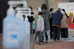 「復興の火」として東京オリンピックの聖火(右奥)が展示される会場では、新型コロナウイルスの世界的流行をうけ、入り口に消毒液(左)が置かれ、間隔をあけて並ぶよう呼びかけられた=岩手県大船渡市で2020年3月23日、和田大典撮影