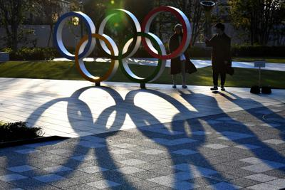 夕日に照らされ影が伸びる日本オリンピック委員会前の五輪マークのモニュメント=東京都新宿区で2020年3月23日、大西岳彦撮影