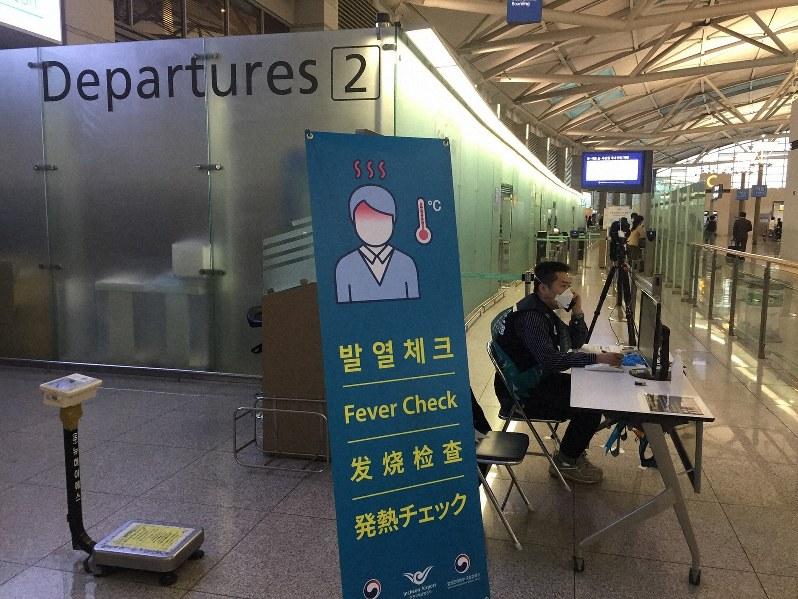 韓国・仁川空港で、出国者が発熱していないかをチェックする職員=2020年3月6日、坂口裕彦撮影
