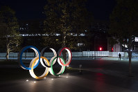 The Olympic rings stand near the New National Stadium in Tokyo, on March 24, 2020. (AP Photo/Jae C. Hong)