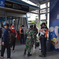 乗降客が行き来する横で警察官や兵士が警戒するバス停留所=ジャカルタで2020年3月23日、武内彩撮影