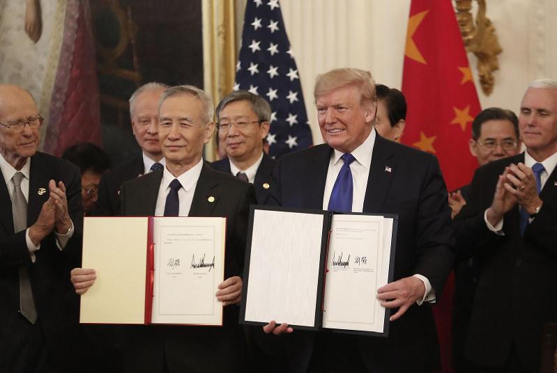 第1段階の合意文書を持つトランプ米大統領(右)と中国の劉鶴副首相(Bloomberg)