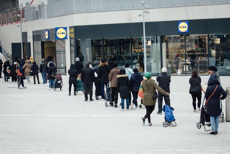 外出禁止令に備え店の前に列を作るパリ市民(Bloomberg)