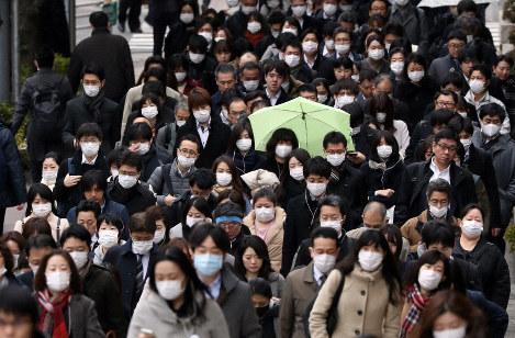新型コロナウイルスへの警戒感から街ではマスクをつけて通勤する人が目立つ=東京都中央区で2020年3月4日、小川昌宏撮影