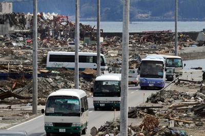 仮設住宅ができるまで内陸部の宿泊施設などに集団避難する人たちを乗せ、宮城県南三陸町の被災地を走るバス。後方は志津川湾。集団避難の第1陣は約500人で、計22台のバスに分乗して出発した。避難所の住民約9500人を対象に行った意向調査では、集団避難を希望したのは約3割だった=2011年4月3日午後0時32分、丸山博撮影
