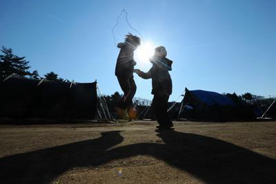 朝日に照らされた避難所の広場で縄跳びをする子どもたち=宮城県女川町で2011年4月5日午前7時41分、津村豊和撮影
