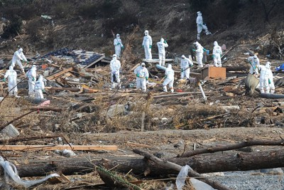 防護服に身を固め、福島第1原発から20キロ圏内の避難指示区域で行方不明者を捜索する警察官。福島第1原発事故の影響で放射線量が高いため捜索が進まず、20キロ圏内はがれきも手つかずの状態となっている。一度も自宅に戻れない避難住民からは、「せめて遺体の回収を早くしてほしい」という強い要望が出ていた=福島県南相馬市で2011年4月7日午後3時20分、佐藤泰則撮影