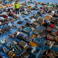 拾得物が並べられた保管所で遺品を捜す人たち=宮城県石巻市の市立福地体育研修センターで2011年4月9日、森田剛史撮影