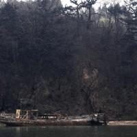 震災発生から1カ月近くたっても放置された船。津波の後に起きた海上火災で、船も木々も焼けた=宮城県気仙沼市で2011年4月9日午後0時8分、丸山博撮影
