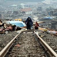 崩れ落ちた線路の上で、思い出の品を探す男性(中央)。「アルバムを探している」と話した=岩手県大槌町で2011年4月9日午後3時27分、小川昌宏撮影
