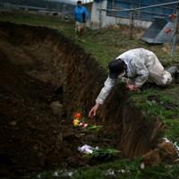 掘られた穴に獣医師らがチューリップなど束ねた花を手向けた。「黙とうします」。皆が目を閉じた。福島県大熊町の繁殖農家がこの春、13頭の牛を安楽死させた。福島原発事故後も、避難先から通い約80頭を飼い続けたが、除染作業により飼育場所の確保が難しくなり、苦渋の決断だった。「私たち家族を経済的に支え、子供を大学にも行かせてくれた」。牛たちは息を引き取ると牧場の片隅に埋葬された=福島県大熊町で4月9日、小出洋平撮影