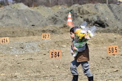 祖母が仮埋葬(土葬)された場所に花を供えに訪れた斎藤佑星さん=宮城県石巻市で2011年4月10日午後0時49分、梅村直承撮影