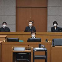新型コロナウイルスの感染対策で、マスク姿で着席する裁判官ら=石川県金沢市の金沢地裁で2020年3月12日撮影