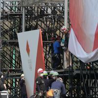東京オリンピックの聖火リレーがスタートする予定だったJヴィレッジの特設会場で撤去作業をする作業員=福島県楢葉町で2020年3月26日午前11時20分、和田大典撮影