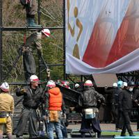 東京オリンピックの聖火リレーがスタートする予定だったJヴィレッジの特設会場で撤去作業をする作業員=福島県楢葉町で2020年3月26日午前11時3分、和田大典撮影