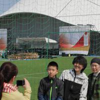東京オリンピックの聖火リレーがスタートする予定だったJヴィレッジの特設会場での撤去作業を見に訪れた家族連れ。「グランドスタートを見に来る予定だった。道で声をかける練習をしてきたけど、来年またここからスタートしてほしいですね」と話した=福島県楢葉町で2020年3月26日午後0時19分、和田大典撮影