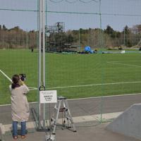 東京オリンピックの聖火リレーがスタートする予定だったJヴィレッジの特設会場での撤去作業を見つめる人=福島県楢葉町で2020年3月26日午後0時3分、和田大典撮影
