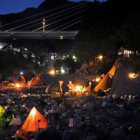 夕暮れの中に浮かび上がるたくさんのテント。キャンプ場の宿泊客らが食事を取ったり、たき火を囲んだりしていた=東京都奥多摩町の川井キャンプ場で2020年3月21日、手塚耕一郎撮影