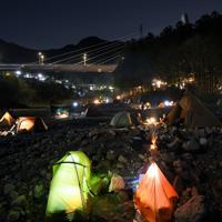 夕暮れの中に浮かび上がるたくさんのテント。キャンプ場の宿泊客らは食事をとったり、たき火を囲んだりと、自由な時間を過ごしていた=東京都奥多摩町の川井キャンプ場で2020年3月21日午後6時49分、手塚耕一郎撮影