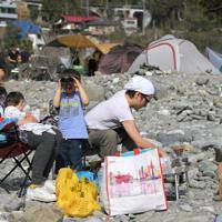 デイキャンプで訪れ、河原で昼食後にくつろぐ家族連れ=東京都奥多摩町の川井キャンプ場で2020年3月21日午後2時22分、手塚耕一郎撮影
