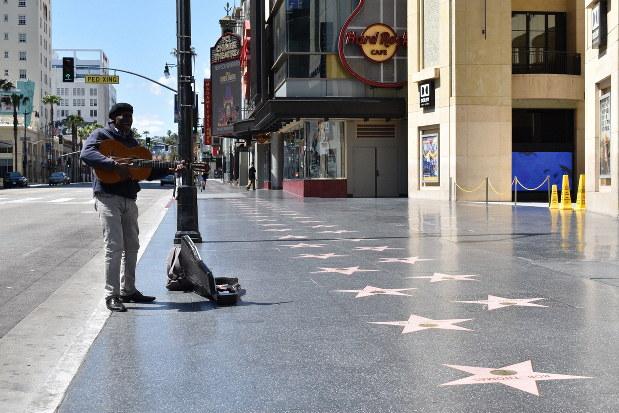 ほぼ無人になったハリウッド中心部の「ウオーク・オブ・フェーム(名声の歩道)」で路上ライブをする男性ミュージシャン=米西部カリフォルニア州ロサンゼルスで2020年3月26日、福永方人撮影