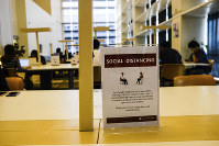 In this March 16, 2020 photo, a sign about social distancing is placed on a table at the National Library in Singapore. (AP Photo/Ee Ming Toh)