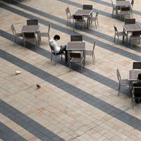 「外出自粛」を受け、人影が少ない東京ミッドタウン周辺。満開の桜が見えるテラスも、空席が目立つ=東京都港区で2020年3月28日午後1時45分、小川昌宏撮影