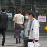 週末の外出を控えるよう都が要請する中、商業施設の臨時休業を知らせる張り紙を見る人たち=東京都新宿区で2020年3月28日午後1時45分、手塚耕一郎撮影