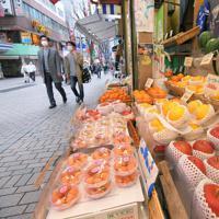 週末の外出を控えるよう都が要請する中、開店していたJR新宿駅近くの果物店。店長代理の男性は「人は普段の週末よりはるかに少ない。売り上げは8割減だよ」とつぶやいた=東京都新宿区で2020年3月28日午後2時15分、手塚耕一郎撮影