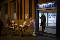 An elderly COVID-19 patient is transferred to an ambulance from a Hospital in Barcelona, Spain, on March 27, 2020. (AP Photo/Felipe Dana)