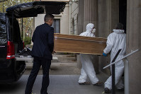 Undertakers carry a coffin to a burial at a Barcelona cemetery during the coronavirus outbreak, Spain, on March 27, 2020. (AP Photo/Emilio Morenatti)