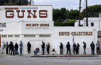 In this March 15, 2020, file photo, people wait in a line to enter a gun store in Culver City, Calif. (AP Photo/Ringo H.W. Chiu, File)