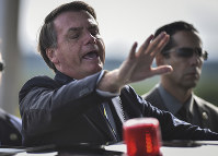 Brazil's President Jair Bolsonaro greets supporters and journalists as he arrives to give a news conference on the new coronavirus at Planalto presidential palace in Brasilia, Brazil, on March 27, 2020. (AP Photo/Andre Borges)