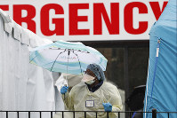 A medical worker holds an umbrella as she checks to see if anyone is waiting in line outside a COVID-19 testing center at Elmhurst Hospital Center in New York, on March 28, 2020. (AP Photo/Kathy Willens)