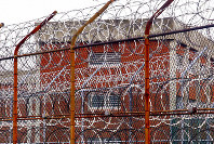 In this March 16, 2011, file photo, a security fence surrounds inmate housing at the Rikers Island correctional facility in New York. (AP Photo/Bebeto Matthews, File)