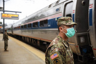 Members of the Rhode Island National Guard look for passengers getting off from a train from New York as it arrives Saturday, March 28, 2020, in Westerly, R.I. (AP Photo/David Goldman)